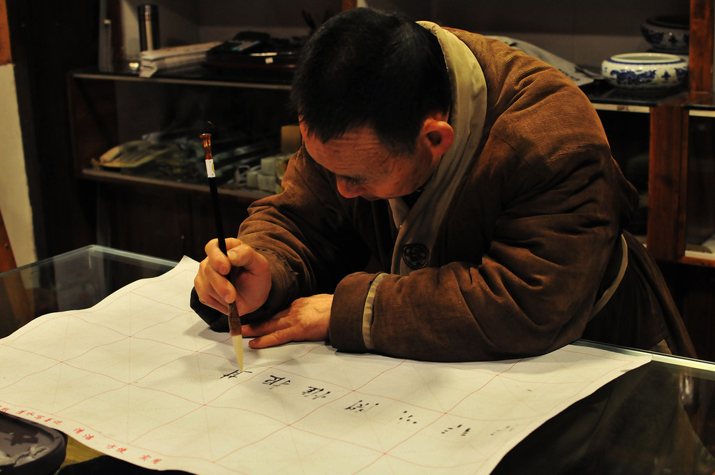 photo of caligrapher writing Chinese characters